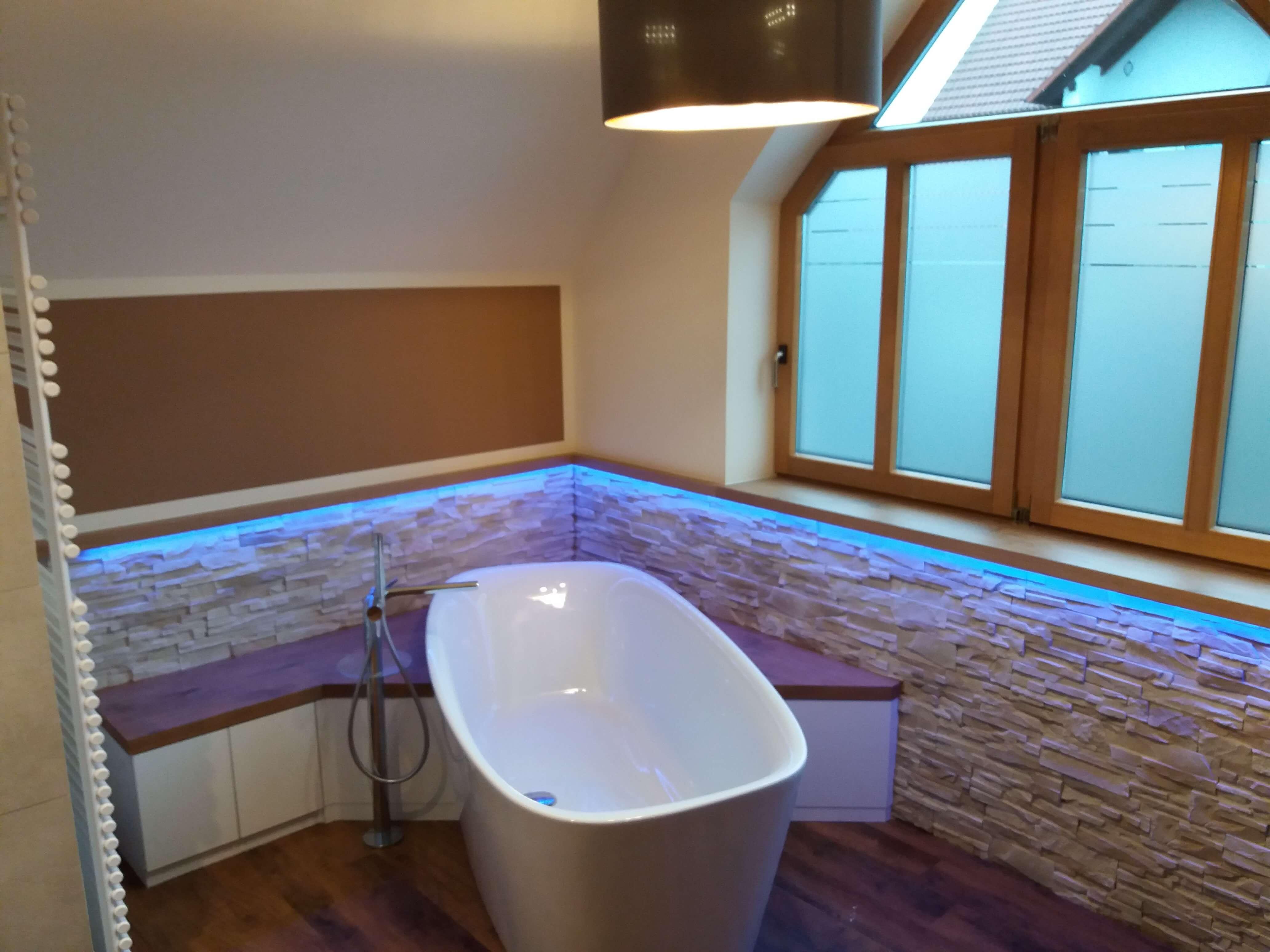 Badezimmer Badewanne vor Steinwand mit LED-Beleuchtung
